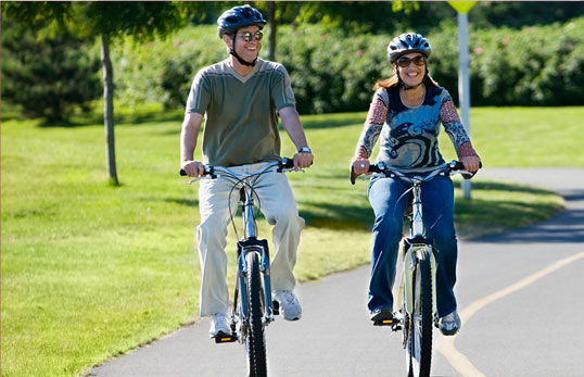 two people riding bikes along a bike path